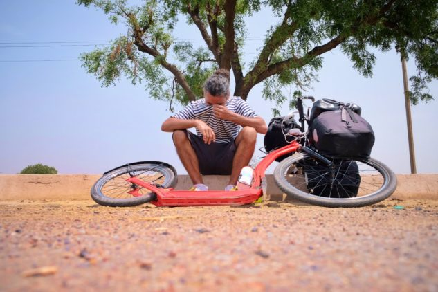 Marek Jelínek se svojí koloběžkou Yedoo Trexx vyčerpaně odpočívá na cestě po Indii