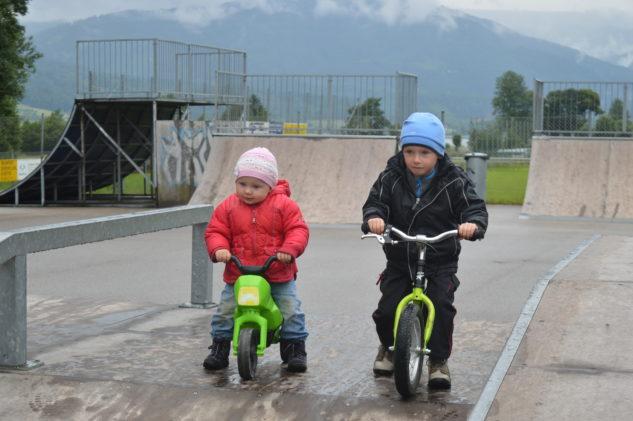 Tomáš na odrážedke a Laura ještě na dětské motorce