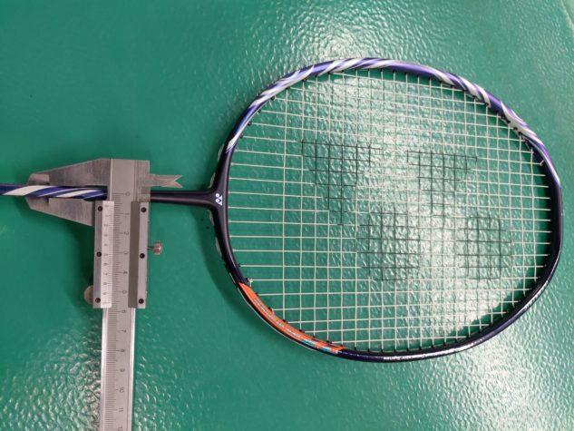 Hřídelka badmintonové rakety Yonex Astrox 100 je ultimátně tenká.